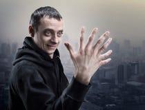 Überraschter Mann betrachtet seine merkwürdige Hand Stockbilder