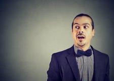 Überraschter Mann, der auf Klatsch hört Stockfotografie