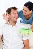 Überraschter Mann, der ein Geschenk von seiner Freundin empfängt stockfoto