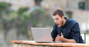 Überraschter Mann, der Inhalt auf einem Laptop in einem Balkon findet stock video footage