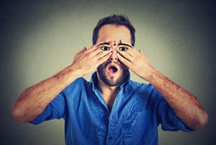 Überraschter Mann mit den Augen gemalt auf seinen Händen Stockbilder