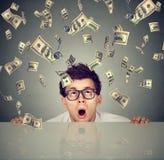 Überraschter Mann unter dem Geldregen, der von unterhalb der Tabelle späht lizenzfreies stockbild