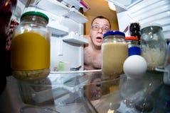 Überraschter Mann untersucht Kühlraum Stockfotos