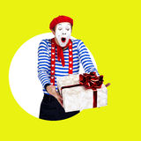 Überraschter Pantomime mit Geschenk Lustiger Schauspieler im Rot Stockfotografie