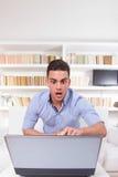 Überraschter Student, der den Laptopmonitor entsetzt betrachtet Stockfotografie