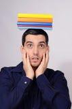 Überraschter Student, der einen Stapel von Büchern auf seinem Kopf hält. Stockbilder