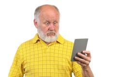 Überraschter und erstaunter älterer kahler Mann mit Spiegel Lizenzfreies Stockbild