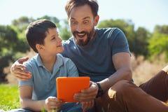 Überraschter Vater, der ein Video mit seinem Sohn aufpasst stockbild