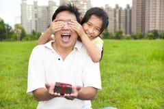 Überraschter Vater, der Geschenkbox vom kleinen Mädchen hält Stockbilder