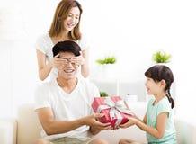 Überraschter Vater, der Geschenkbox von der Frau und von der Tochter empfängt stockfotos