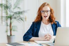 Überraschter weiblicher Angestellter des Ingwers hat Job, entwickelt das neue srategy Geschäft, aufwirft vor geöffneter Laptop-Co lizenzfreie stockbilder