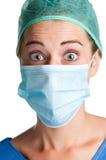 Überraschter weiblicher Chirurg mit Gesichtsmaske stockfotografie