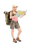 Überraschter weiblicher Wanderer, der eine Karte betrachtet Stockbild