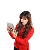 Überraschtes asiatisches Mädchen, das Tablette hält Stockbilder