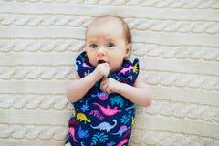 Überraschtes Baby des einmonatigen Babys, das auf gestrickter Decke liegt Stockfotos