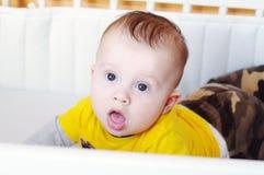 überraschtes Baby liegt auf einem Magen in einem Bett Stockfotos