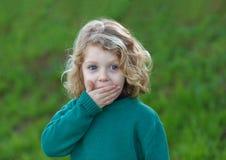Überraschtes blondes Kind, das seinen Mund bedeckt Stockfotografie