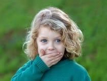 Überraschtes blondes Kind, das seinen Mund bedeckt Lizenzfreies Stockfoto