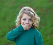 Überraschtes blondes Kind, das seinen Mund bedeckt Stockbild