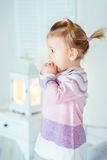 Überraschtes blondes kleines Mädchen mit dem Pferdeschwanz, der auf Bett bleibt Lizenzfreie Stockfotos