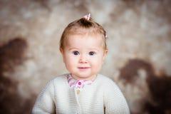 Überraschtes blondes kleines Mädchen mit großen grauen Augen und prallen Backen Stockbilder