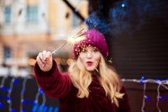 Überraschtes blondes Mädchen, das brennende Bengal-Lichter beim Chris hält Stockfotografie