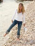 Überraschtes blondes Mädchen durch das kalte Meer Stockbild