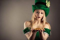Überraschtes blondes Mädchen im Bild des Kobolds mit Goldmünzen in den Händen Stockbild