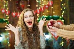 Überraschtes blondes Mädchen nimmt Geschenkring im roten Kasten Stockbild