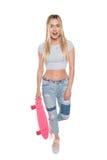 Überraschtes blondes Mädchenholdingskateboard und Betrachten der Kamera lokalisiert auf Weiß Lizenzfreies Stockfoto