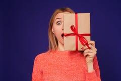 Überraschtes blondes versteckendes Gesicht hinter Geschenkbox Lizenzfreies Stockfoto