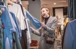 Überraschtes Einkaufen der jungen Frau in einer Boutique stockfoto