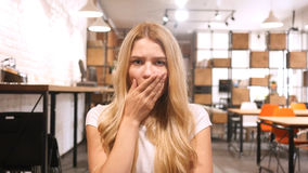 Überraschtes, entsetztes blondes Mädchen, das im Büro sitzt lizenzfreie stockbilder