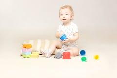 Überraschtes entzückendes Baby, das auf dem Boden sitzt und mit seinen Spielwaren spielt Stockfoto