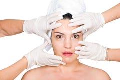 Überraschtes Frauengesicht in den chirurgischen Handschuhhänden Stockbilder
