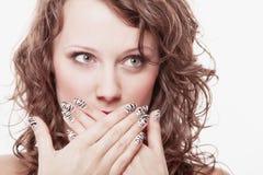 Überraschtes Frauengesicht, Mädchen, das ihren Mund über Weiß bedeckt Stockfotografie