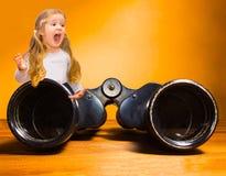 Überraschtes glückliches kleines Mädchen und Ferngläser über orange Hintergrund Lizenzfreies Stockbild