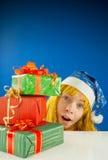 Überraschtes jugendlich Mädchen, das von hinten Geschenke schaut Stockfotografie