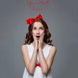 Überraschtes jugendlich Mädchen mit rotem Bogen auf Kopf Stockfotografie