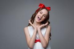 Überraschtes jugendlich Mädchen mit rotem Bogen auf Kopf Stockfotos