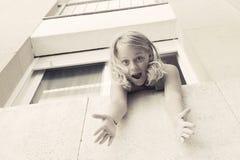 Überraschtes junges blondes kaukasisches Mädchen im Fenster Lizenzfreies Stockfoto