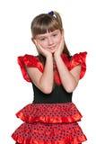 Überraschtes junges Mädchen in einem roten Tupfenkleid Stockfotos