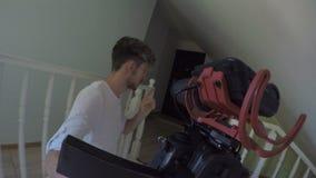 Überraschtes junges männliches vlogger, das oben zu einer beweglichen Berufskamera spricht und zu Hause passt - stock video footage