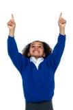 Überraschtes junges Schulmädchen, das aufwärts anzeigt Lizenzfreie Stockbilder