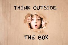 Überraschtes Kind, das durch Loch der Pappe schaut stockbilder
