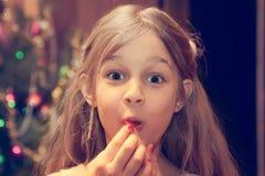 Überraschtes Kind, das Kamera während des Weihnachten Feiertage betrachtet, nachdem Weihnachtsgeschenk empfangen worden ist Stockfotografie