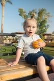 Überraschtes Kind, das mit zwei Orangen auf Bank sitzt Stockbilder