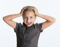 Überraschtes Kind des kleinen Mädchens mit den Händen auf ihrem Kopf Lizenzfreies Stockfoto