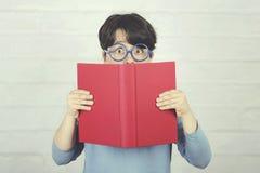 Überraschtes Kind mit den Gläsern, die ein Buch halten lizenzfreies stockbild
