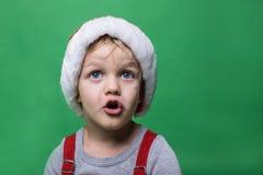 Überraschtes Kind mit roter Santa Claus-Kappe, die oben schaut Große blaue Augen Weihnachtsniederlassung und -glocken Stockfotografie